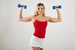 Привлекательная женщина при атлетическое тело держа гантели на белизне Стоковое Изображение
