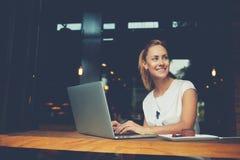 Привлекательная женщина при красивая улыбка сидя с портативной сет-книгой в кофейне Стоковая Фотография RF