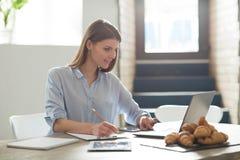 Привлекательная женщина работая на компьтер-книжке Стоковое фото RF