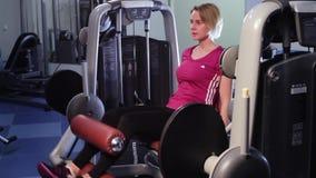 Привлекательная женщина разрабатывает на машине прессы ноги на спортзале акции видеоматериалы