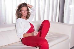 Привлекательная женщина сидя на кресле и думать Стоковые Изображения