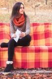 Привлекательная женщина сидя на стенде с таблеткой Стоковое фото RF