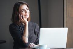Привлекательная женщина сидя на таблице говоря телефоном Стоковое Изображение