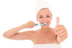 Привлекательная женщина с большими пальцами руки зубной щетки вверх Стоковое Фото
