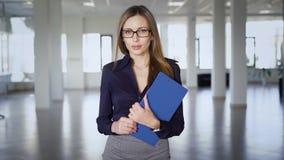 Привлекательная женщина с бумагами в офисе Молодая женщина держа таблетку с бумагами в пустых размерах офиса сток-видео