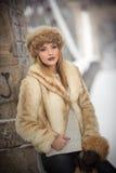 Привлекательная женщина с коричневыми крышкой и курткой меха наслаждаясь зимой Взгляд со стороны модной белокурой девушки предста Стоковое фото RF