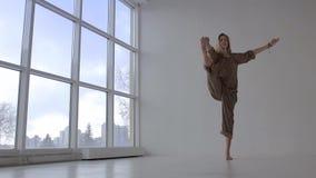 Привлекательная женщина с представлением рук-к-больш-пальца ноги совершенного тела практикуя выдвинутым видеоматериал