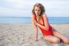 Привлекательная женщина с совершенным телом в красном бикини представляя для камеры на пляже в лете Стоковое Фото