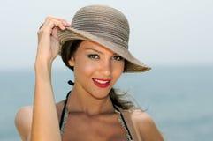 Привлекательная женщина усмехаясь с шляпой солнца на тропическом пляже стоковое фото
