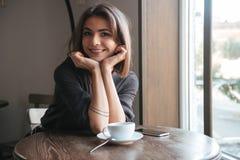 Привлекательная жизнерадостная молодая дама в кофе кафа выпивая Стоковая Фотография RF