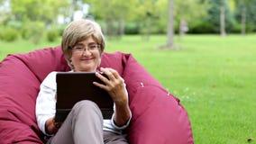 Привлекательная зрелая женщина используя цифровую таблетку в парке сток-видео