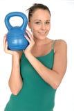 Привлекательная здоровая молодая женщина поднимая вес колокола чайника 5kg Стоковое Изображение