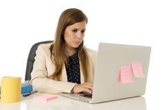 Привлекательная коммерсантка на ее 30s сидя на стуле офиса работая на компьтер-книжке Стоковое Фото