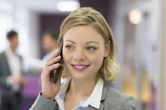 Привлекательная коммерсантка на мобильном телефоне в современном офисе Стоковые Фото
