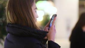 Привлекательная коричнев-с волосами блестящая девушка принимая фото ее друг ` s красивый на террасе торгуя центра, устоичивой видеоматериал