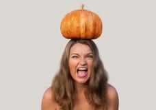 Привлекательная кричащая девушка с тыквой хеллоуина на ее голове Стоковое Изображение