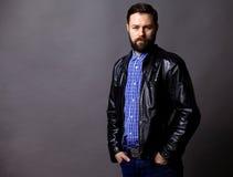 Привлекательная куртка молодого человека нося кожаная на сером цвете стоковое изображение rf