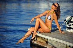 Привлекательная маленькая девочка в бикини и солнечных очках представляя довольно на пристани Стоковая Фотография RF