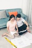 Привлекательная молодая азиатская взрослая пара смотря дом планирует Стоковая Фотография