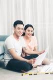 Привлекательная молодая азиатская взрослая пара смотря дом планирует Стоковое Изображение RF