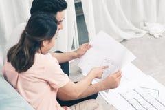 Привлекательная молодая азиатская взрослая пара смотря дом планирует Стоковое фото RF