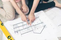 Привлекательная молодая азиатская взрослая пара смотря дом планирует Стоковое Фото
