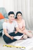 Привлекательная молодая азиатская взрослая пара смотря дом планирует Стоковые Изображения