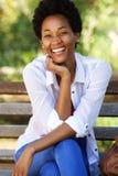 Привлекательная молодая африканская женщина сидя на скамейке в парке Стоковые Изображения RF