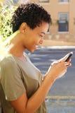 Привлекательная молодая Афро-американская женщина смотря мобильный телефон Стоковая Фотография RF