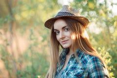 Привлекательная молодая белокурая женщина в голубой соломенной шляпе рубашки шотландки наслаждаясь ее временем вне прятать от сол Стоковое фото RF