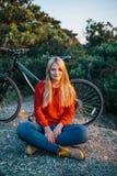 Привлекательная молодая белокурая женщина на предпосылке велосипеда и леса Стоковая Фотография RF