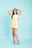 Привлекательная молодая женщина брюнет в желтом платье на голубой предпосылке стоковые фото