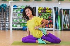 Привлекательная молодая женщина брюнет сидя на циновке нагревая перед тренировкой протягивающ ее quadriceps в спортзале усмехаясь Стоковая Фотография RF