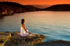 Привлекательная молодая женщина в положении йоги на красивом пляже стоковая фотография