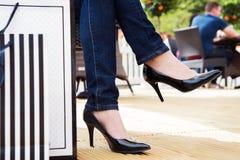 Привлекательная молодая женщина в сексуальных черных высоких пятках наслаждаясь проломом после успешных покупок Стоковая Фотография RF