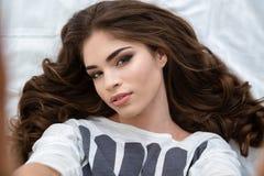 Привлекательная молодая женщина лежа и делая selfie стоковая фотография rf