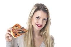 Привлекательная молодая женщина есть пиццу Стоковое фото RF