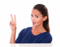 Привлекательная молодая женщина делая знак победы Стоковое Изображение