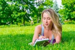 Привлекательная молодая женщина делая примечания в тетради Стоковое Изображение RF
