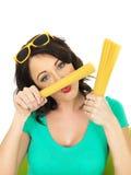 Привлекательная молодая женщина играя с держать пригорошни высушенных макаронных изделий Стоковые Фотографии RF