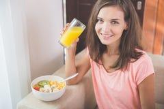 Привлекательная молодая женщина наслаждаясь апельсиновым соком Стоковые Изображения