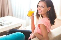 Привлекательная молодая женщина наслаждаясь апельсиновым соком Стоковая Фотография