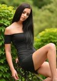 Привлекательная молодая женщина наслаждаясь ее временем снаружи в парке стоковое изображение