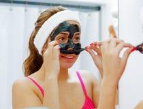 Привлекательная молодая женщина нося розовую верхнюю часть и белый держатель, извлекая черную обработку маски от стороны использу Стоковая Фотография RF