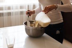 Привлекательная молодая женщина добавляя молоко к муке стоковая фотография