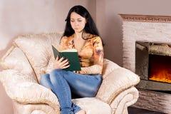 Женщина читая книгу около пожара Стоковые Изображения RF