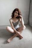 Привлекательная молодая женщина одела в серой пустой футболке представляя на предпосылке бетонной стены Стоковое Изображение RF