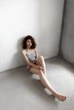 Привлекательная молодая женщина одела в серой пустой футболке представляя на предпосылке бетонной стены Стоковое Изображение