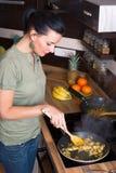 Привлекательная молодая женщина подготавливая обед стоковые фото