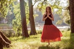 Привлекательная молодая женщина практикует йогу и делает asana Vrikshasana в утре Стоковые Фото